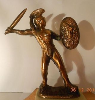 Römischer Schwertkämpfer Aus Rötlichem Metall Auf Weißem Marmorsockel Bild