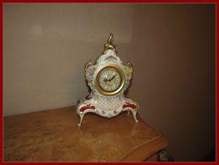 Porzellan Uhr Auf Vier Füßen Stehend Mit Blumen Abgesetzt Bild