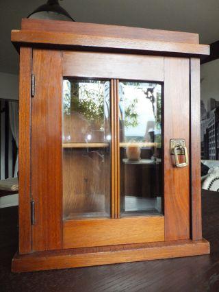 Antikes Wandschränkchen Mit Glas In Der Tür Und Verziertem Messingbeschlag Bild
