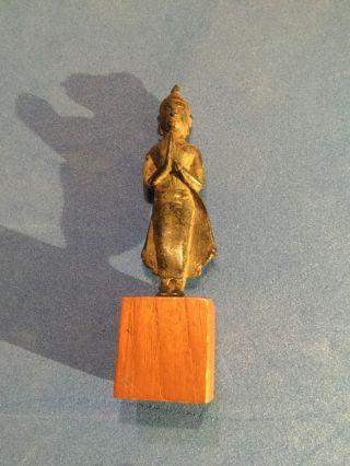 Budistische Figur Aus Metall Auf Holzklötzchen Bild
